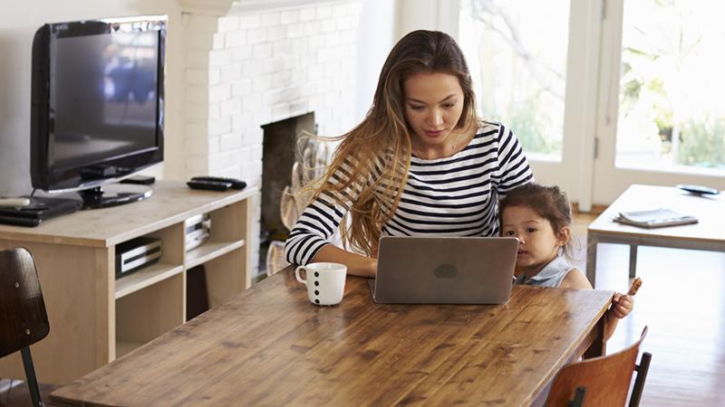Kvinna sitter vid bord med datorn.