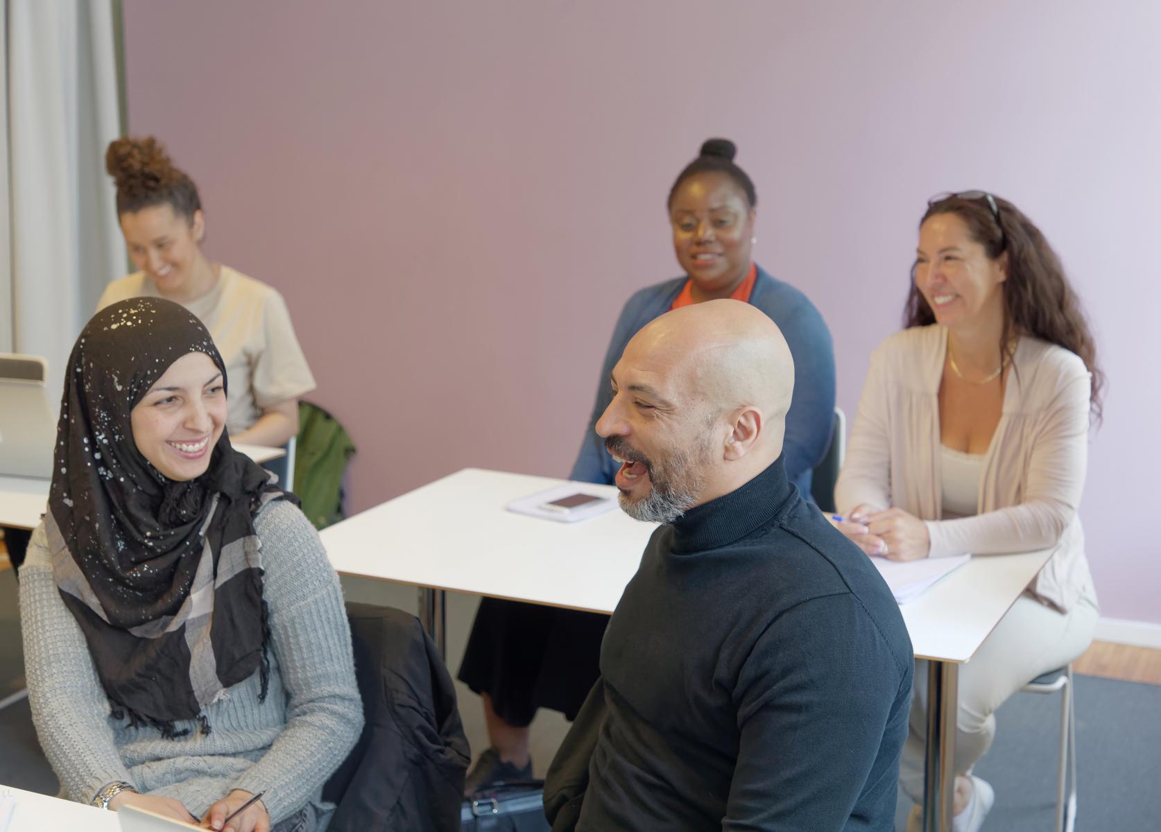En grupp på fem vuxna studenter sitter i ett klassrum och pratar med varandra.