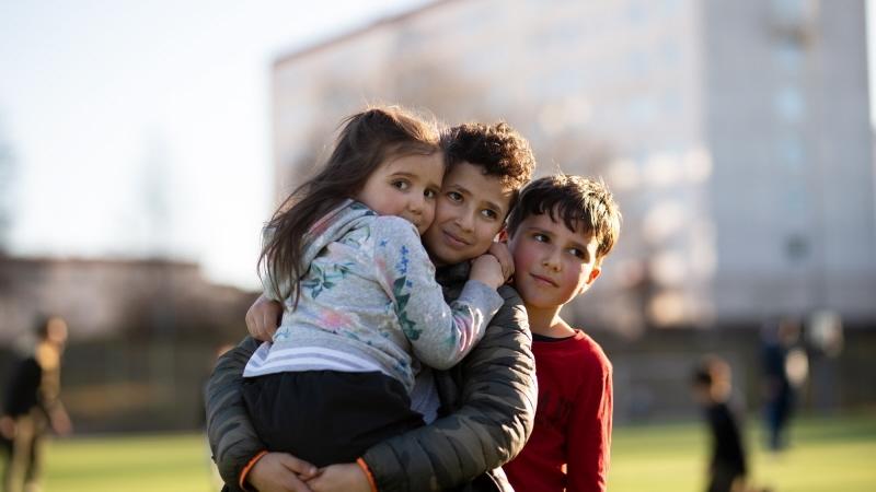 Tre barn; en flicka och två pojkar står på en fotbollsplan och tittar mot kameran.