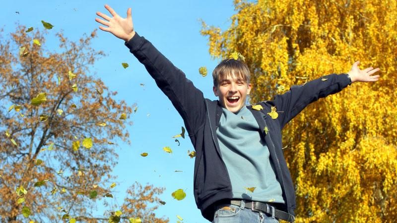 En glad kille kastar höstlöv i luften.