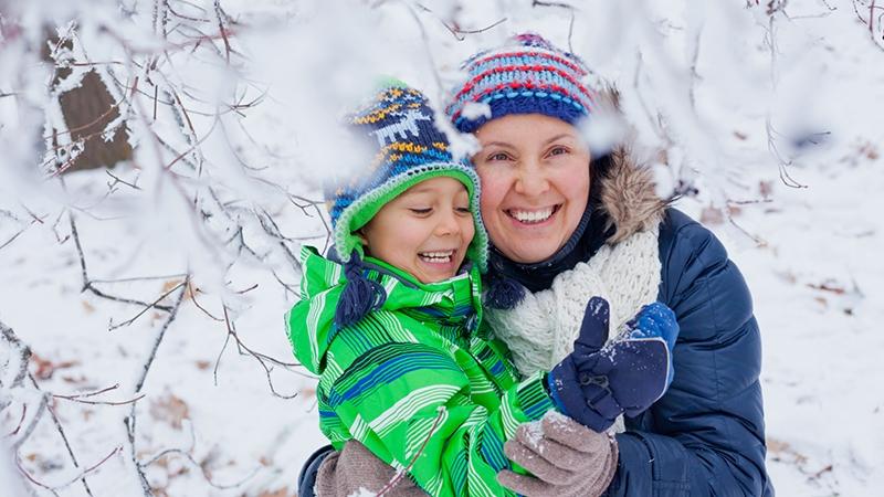 En vinterklädd, glad pojke och mamma under en snöig trädgren