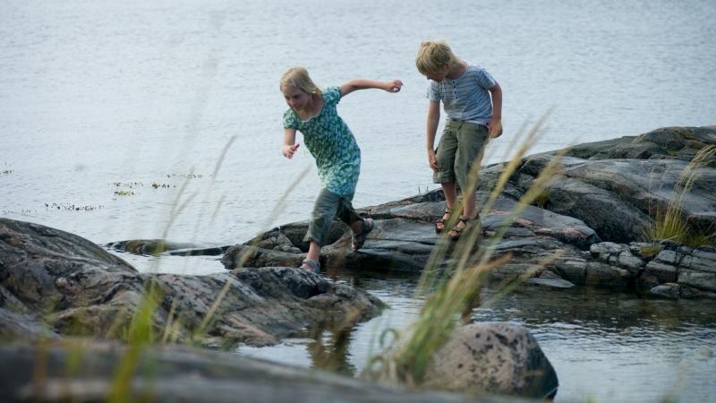 En flicka och en pojke balanserar på stenar på vattnet.