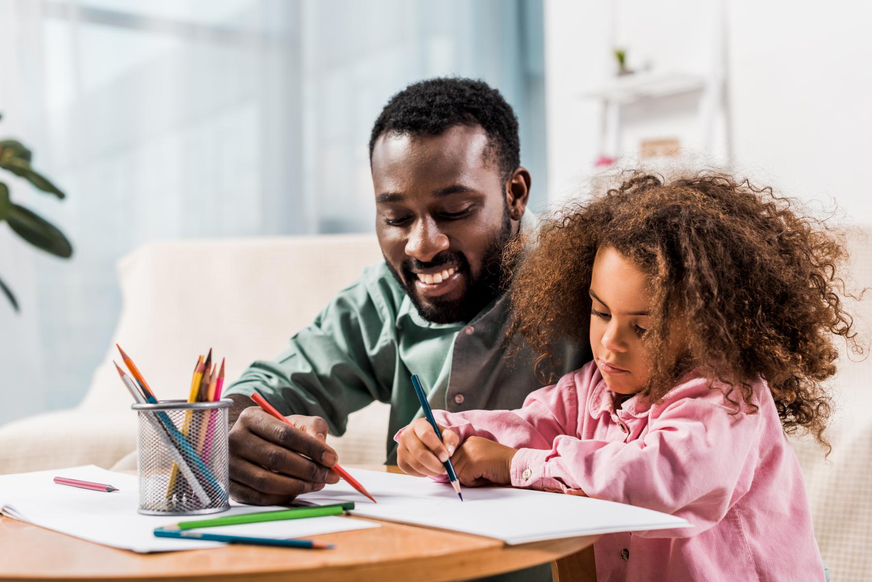 En pappa med sin dotter sitter vid ett bord och ritar med färgpennor.
