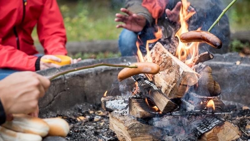 Eld som brinner och händer som grillar korv på pinne och galler.