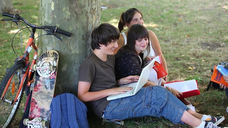 Ungdomar utomhus vid en trästam.
