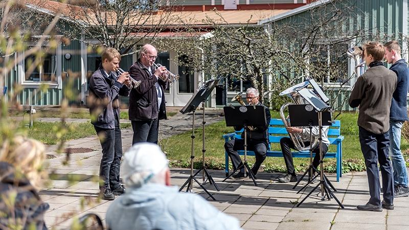 Seniorer njuter av musik i vårsolen.