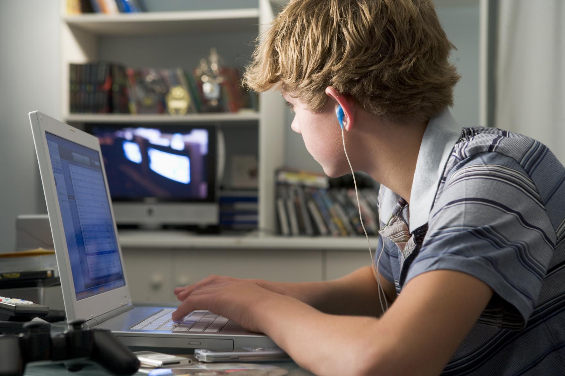 Pojke sitter vid en dator i hemmamiljö