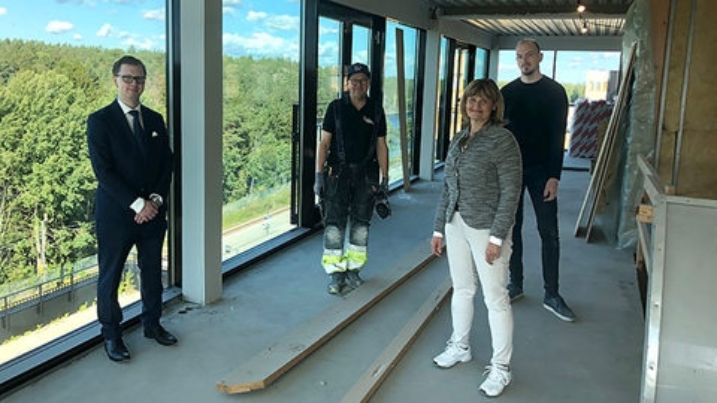 I de nya lokalerna, framför stora fönster står: Martin Strömvall, äldrenämndens ordförande, Tomas Bermbeck, byggarbetare, Siw Lidestål, social- och äldredirektör och Magnus Kinnander, projektledare.