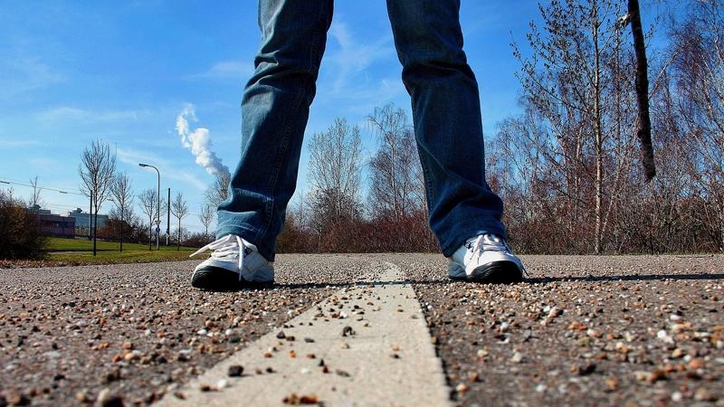 Jeansklädda ben med vita gympaskor står på en grusig gångbana