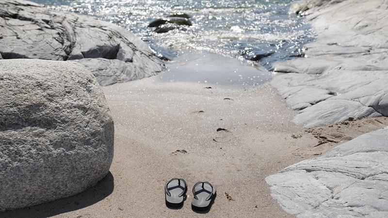 Badtofflor i sanden i vattenbrynet