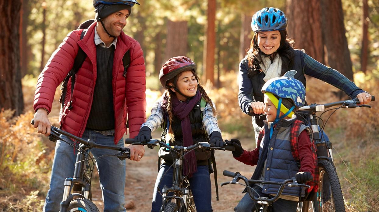 Familj med cyklar längs en gångväg i skogsmiljö