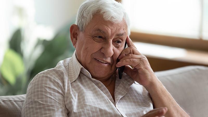 En äldre man ler och talar i telefonen