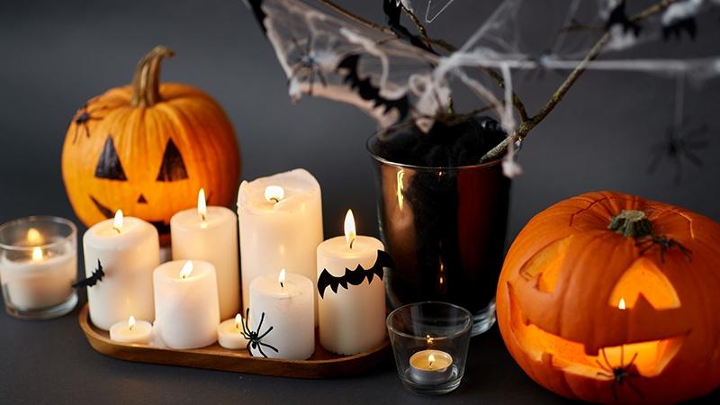 Flera tända ljus dekorerade med fladdermöss av papper och leksaksspindlar, två halloweenpumpor med spindlar på och en vas med dekorationsspindelnät och pappersfladdermöss