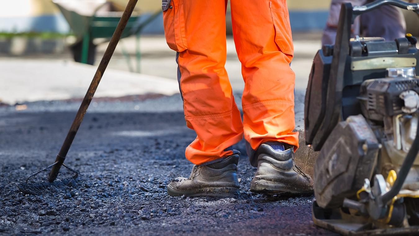 Orangeklädda ben som asfalterar en väg