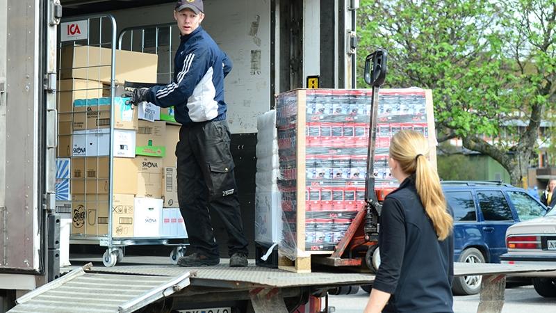 En lastbilschaufför levererar varor till butikspersonal.