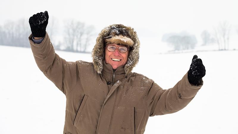 En glad senior med vinterjacka och handskar
