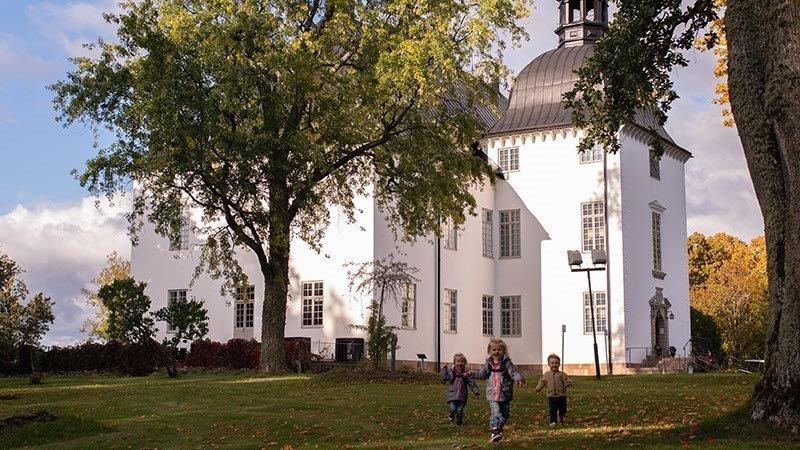 Tre små barn som springer mot kameran i en park. En vit slottsbyggnad i bakgrunden.