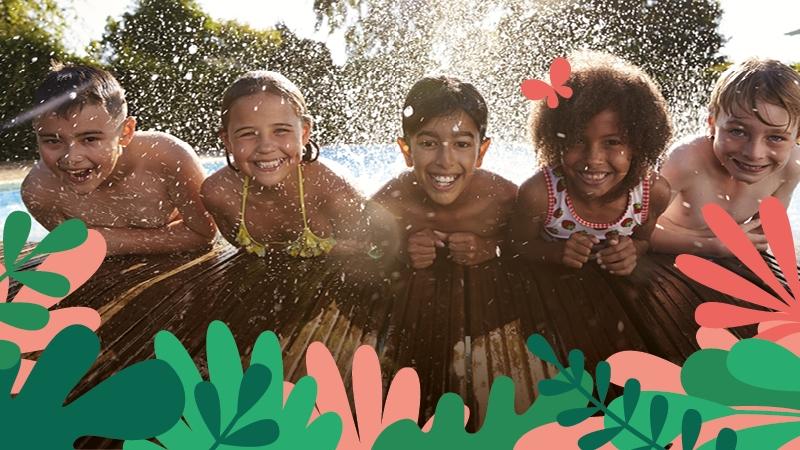 Fyra glada barn hänger på en brygga med vatten som bakgrund.